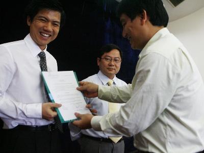 Bí thư thứ nhất TƯ Đoàn trao quyết định cho nhà báo Đoàn Công Huynh (bên trái) và nhà báo Lê Xuân Sơn. Ảnh: Hồng Vĩnh