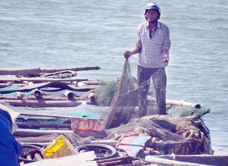 Ông Nguyễn Cường bên chiếc lồng bè bị cắt lưới. Đ.C