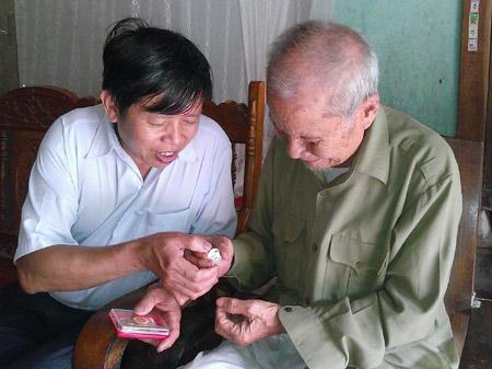 Ông Nguyễn Văn Khả và kỷ vật là chiếc huy hiệu chiến sĩ Điện Biên.