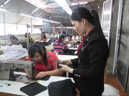 Chị Phương Em (đứng) hướng dẫn công nhân may.