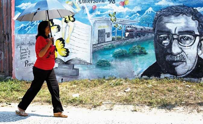 Một phụ nữ đi ngang qua bức tranh tường tôn vinh Gabriel García Márquez ở Aracataca, Colombia,  hôm 18.4.2014, ngày nhà văn tạ thế. Ảnh: TL