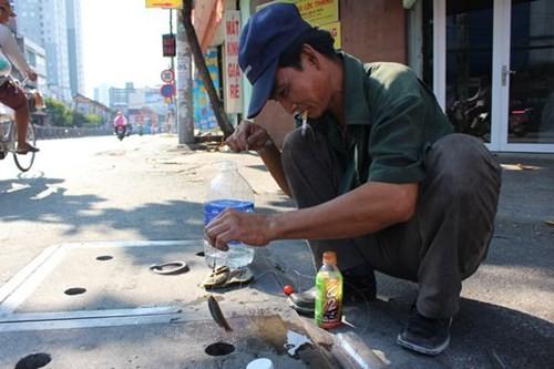Anh Nguyễn Văn Bảy ngồi câu cá ở nắp cống hộp ngay đoạn giao nhau giữa Ngô Văn Sở và Nguyễn Tất Thành, bất chấp sự nguy hiểm