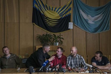 Thị trưởng tự phong Vyachislav Ponomaryov, (thứ 2 từ trái sang) nói chuyện với các thành viên của nhóm các nhà quan sát quân sự quốc tế bị Lực lượng dân quân địa phương bắt giữ trong cuộc họp báo hôm qua.