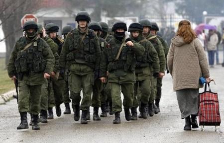 Một phụ nữ đi qua một nhóm binh sĩ được cho là lính Nga tại Crimea