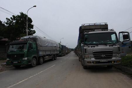 Hàng dài xe tải nối đuôi nhau chờ đợi đoạn đường được sửa chữa.