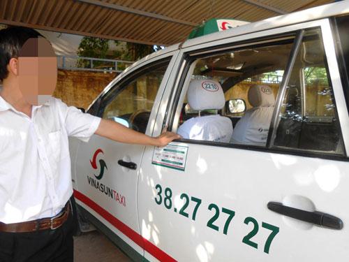 Tài xế T.H.N bên chiếc taxi bị vỡ kính - Ảnh: Phước Hiệp