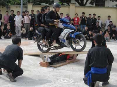 Môn sinh võ phái Nam Hồng Sơn (tại Long Biên, Hà Nội) biểu diễn nằm trên bàn đinh cho xe máy cán qua người. (nguồn CAND.com)