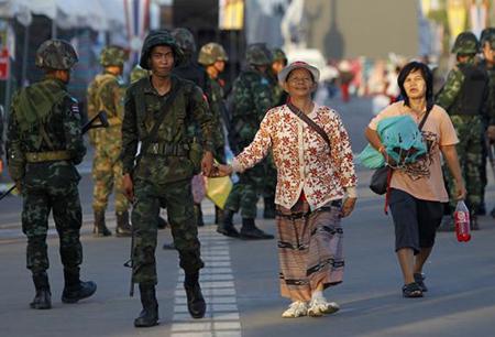 Một binh sỹ Thái Lan cầm tay một phụ nữ biểu tình của phe