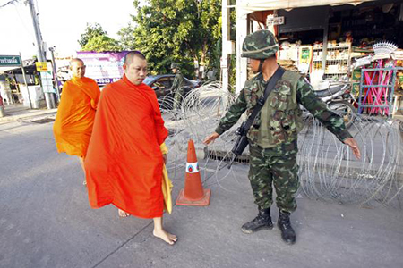 Những nhà sư đi bộ qua  một trạm kiểm soát quân sự gần địa điểm cắm trại của phe