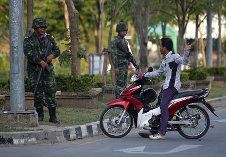 """Một người chạy xe máy nói chuyện với các binh sĩ Thái Lan trang bị vũ trang đang ngăn chặn giao giao thông trên một tuyến đường lớn gần nơi cắm trại của lực lượng """"Áo Đỏ"""" ở tỉnh Nakhon Pathom, ngoại ô Bangkok ngày 22-5-2014"""