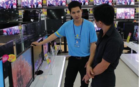 Mặt hàng tivi đang được người tiêu dùng quan tâm trong mùa World Cup 2014. Trong ảnh: khách được nhân viên bán hàng của Dienmay.com tư vấn  sản phẩm. Ảnh: Kim Tuyến