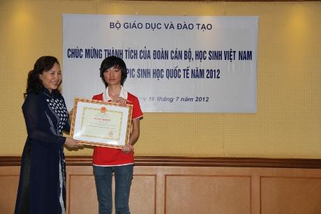 Thứ trưởng Nguyễn Thị Nghĩa trao bằng khen của Bộ Giáo dục và Đào tạo cho em Nguyễn Thu Trang - người đoạt Huy chương bạc. Ảnh: Trường Phong