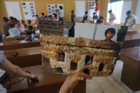 Một người phụ nữ cầm tấm ảnh do mình chụp được  trưng bày tại triển lãm.
