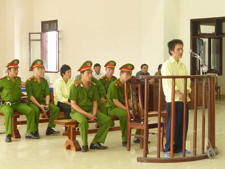 Bị cáo Vũ (đứng) và Phú (áo trắng, ngồi thứ 2 từ trái sang) tại phiên xét xử ngày 22.7.