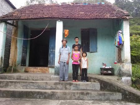Nam cùng ông nội và các em nhỏ trước ngôi nhà của mình.