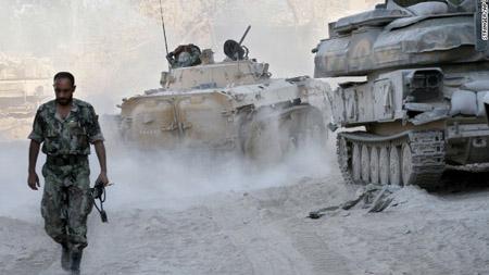 Một người lính Syria đi trên đường phố tan hoang trong ngày 25.8.