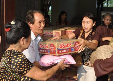Nhà báo Lê Minh (phải) trao hàng cứu trợ cho bà con vùng lũ ở Quảng Bình.