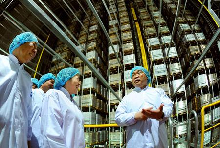 Phó Thủ tướng Hoàng Trung Hải (phải) tham quan hệ thống kho thông minh đầu tiên và lớn nhất  tại Việt Nam nhân ngày khánh thành Nhà máy Sữa Việt Nam.