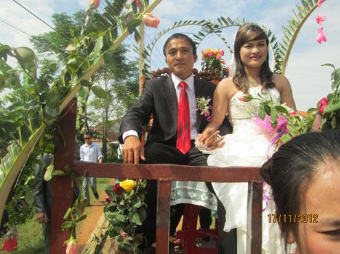 Cô dâu, chú rể nắm tay nhau, hãnh diện ngồi trên xe công nông diễn hành quanh xóm. Ảnh: Viết Văn