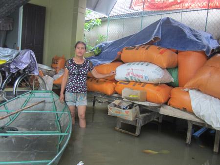 Chị Nguyễn Thị Hoa lo ngại vì số thóc bị ướt vừa được kê cao lên trong ngày 18.10.