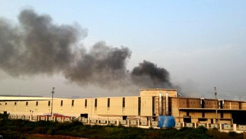 Đến 9h sáng nay, ngọn lửa vẫn âm ỉ trong khu vực giữa kho sản xuất, cột khói đen bốc cao.