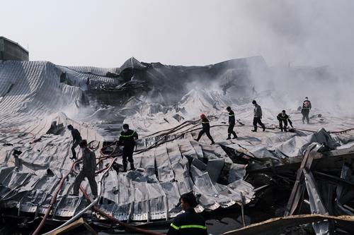 Mái nhà xưởng sụp đổ hoàn toàn trong khi khói vẫn tiếp tục bốc lên.