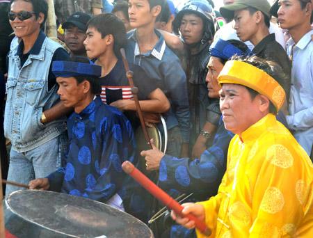 Bà Lê Thị Tá nghiêm trang trong trang phục áo dài, khăn đóng đánh trống chầu tại một buổi hát tuồng