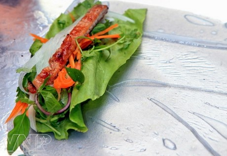 Trải bánh tráng ra đĩa xếp 1 lá rau xà lách, một ít rau thơm, mùi, hành tây, cà rốt, thịt nướng sau đó cuốn tròn lại.