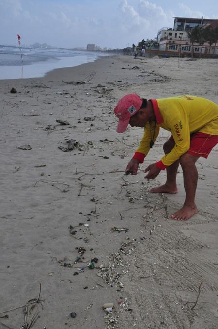 Dầu vón cục dày đặc ở các bãi biển du lịch của Đà Nẵng khiến nhân viên Ban quản lý không thể thu gom hết được.