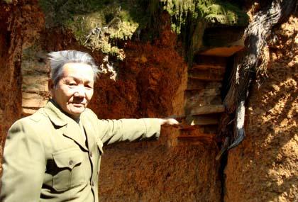 Ông trưởng làng Trần Văn Ngoang bên một ngôi mộ Hán lộ ra bên vách núi Rùa.