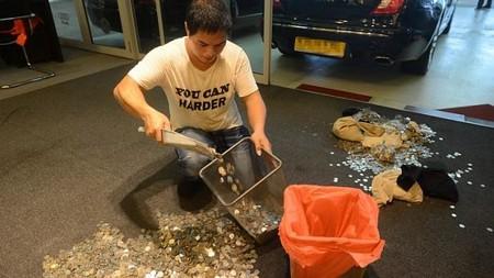 Nhân viên của cửa hàng xe đang xúc đống tiền xu bỏ vào túi nhựa để trả lại cho ông Lester