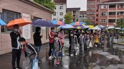 Xúc động cảnh 30 giáo viên xếp hàng dài che ô cho học sinh đến trường