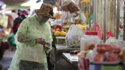 ẢNH: Người dân mặc áo mưa, trùm kín khi đi chợ giữa nắng 37 độ C để phòng dịch Covid-19