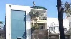 Nam thanh niên khỏa thân, đứng trên nóc nhà la hét