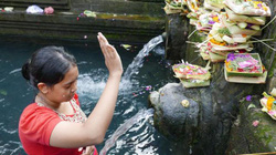 Chắp tay cầu nguyện và tắm gội dưới dòng nước thánh tại Bali