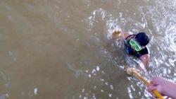 Các thợ lặn ngụp trong nước, tìm thi thể nạn nhân bị bác sĩ thả sông