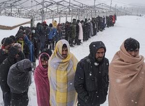 Ảnh: Xót xa cảnh người di cư quấn chăn quanh người chờ nhận thức ăn dưới mưa tuyết