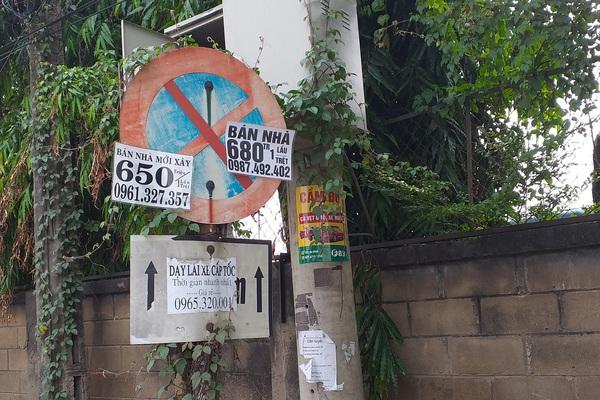 Biển báo giao thông dán chi chít quảng cáo