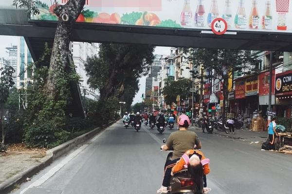 Thót tim bé gái ngủ gục, nằm hẳn ra yên xe máy trên phố Hà Nội